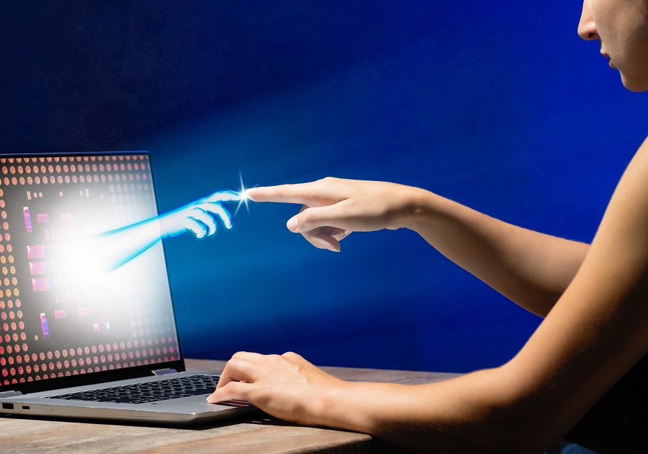 Image conveying virtual reality - hand comes out of laptop screen and finger touches the person's finer