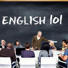 "Teacher in a classroom, with ""English 101"" written on a blackboard"