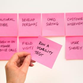 "Post-it notes on a white board, with a hand holding a note that reads ""Run a usability test"""