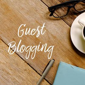 "A table with a coffee cup, glasses, notebook, pen, and the words ""Guest Blogging"""