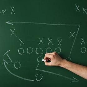 chalkboard with football strategies written on it