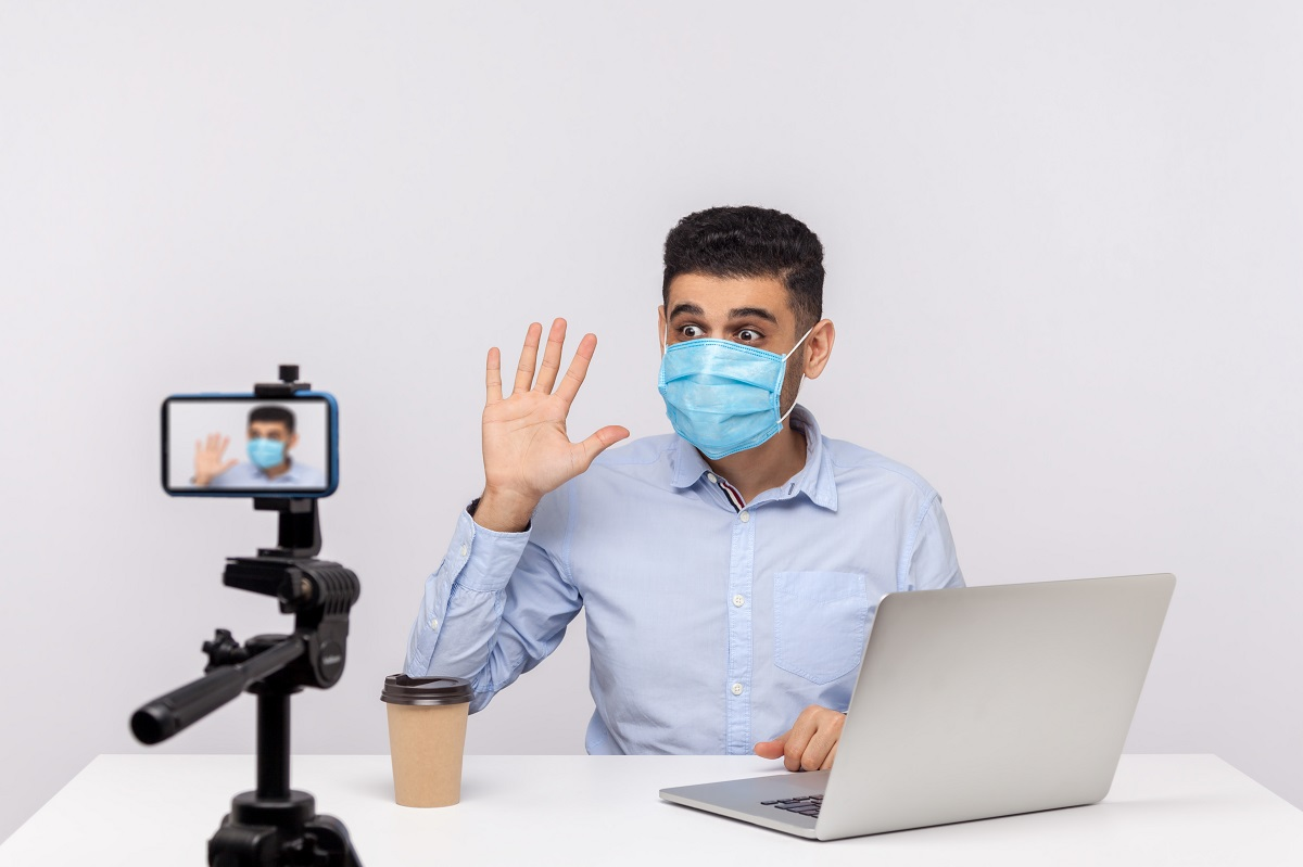 Male blogger in medical mask making video, online streaming about coronavirus news, giving tips on using protect filter against contagious disease. indoor studio shot isolated on white background